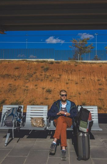 Man with luggage sitting on chair against wall at railroad station platform