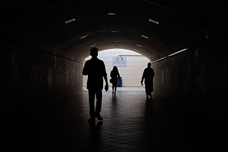 Rear view of silhouette people walking in subway
