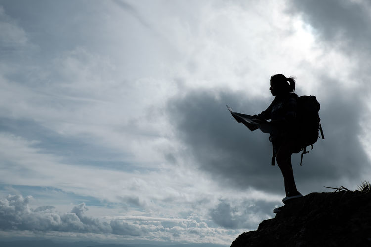 Low Angle View Of Silhouette Woman With Backpack Standing Against Cloudy Sky