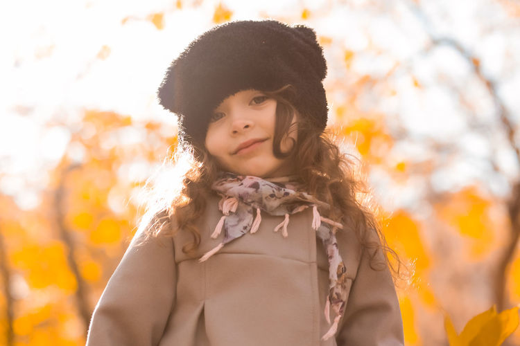 Close-up portrait of smiling girl standing during autumn
