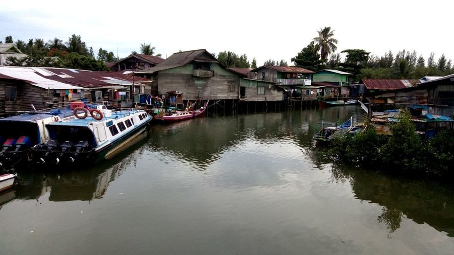 pelabuhan tradisional Reflections In The Water Village On The Sea Water Stilt House Tradition Reflection House Village Architecture Sky Building Exterior Built Structure Floating On Water Boathouse Standing Water Calm Boat Canal Moored Floating Houseboat