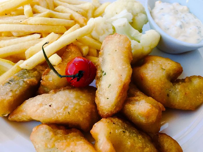 Close-up of fresh fish and chips served in plate