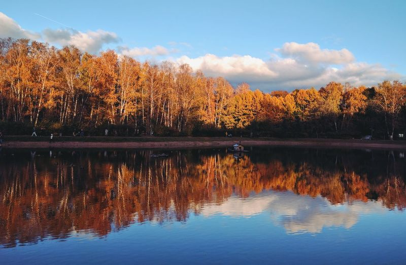 Scenic view of calm lake against sky during autumn