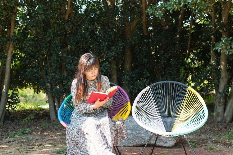 Full length of girl holding umbrella against trees