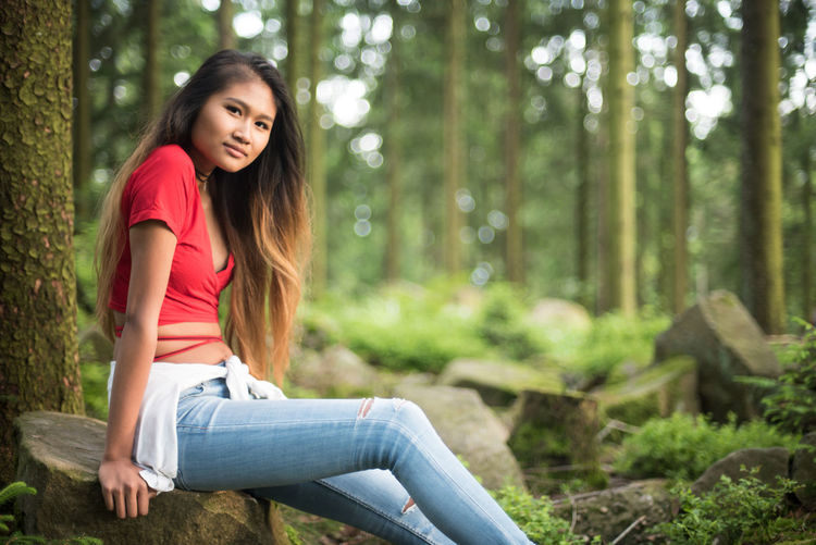 Portrait on young woman sitting on rock by tree trunks in forest
