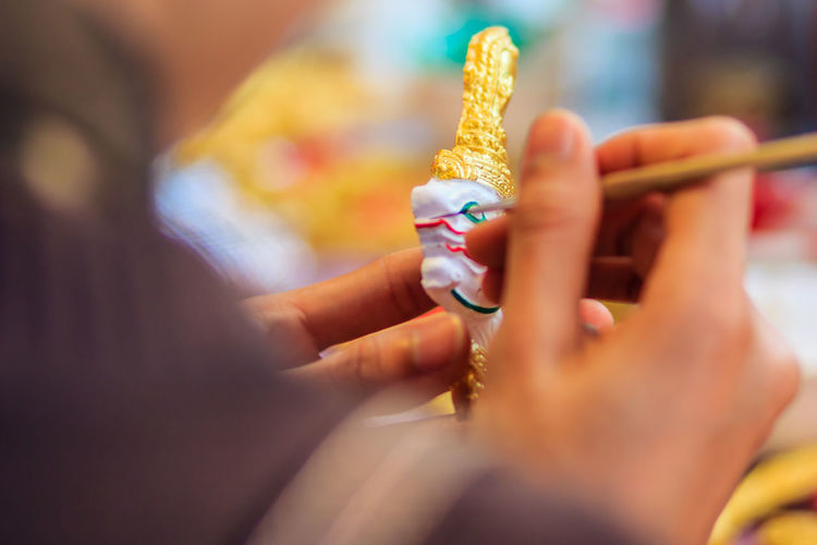 Cropped image of sculptor painting souvenir