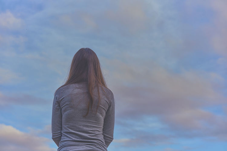 Rear View Of Woman Standing Against Cloudy Sky