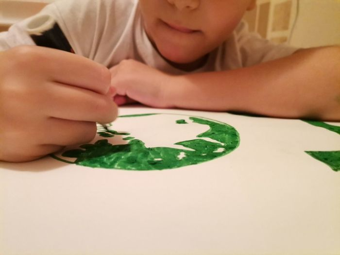 Close-up of boy playing with tattoo on table