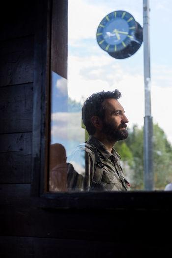 Smiling man looking away seen through window