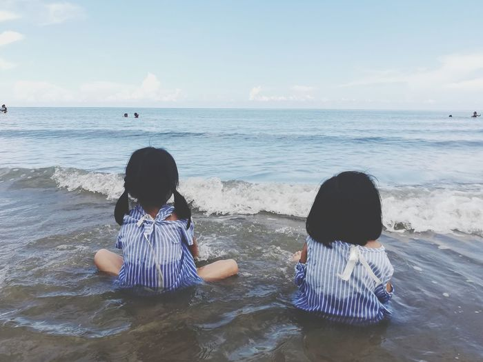 Rear View Of Sisters Sitting At Beach Against Sky