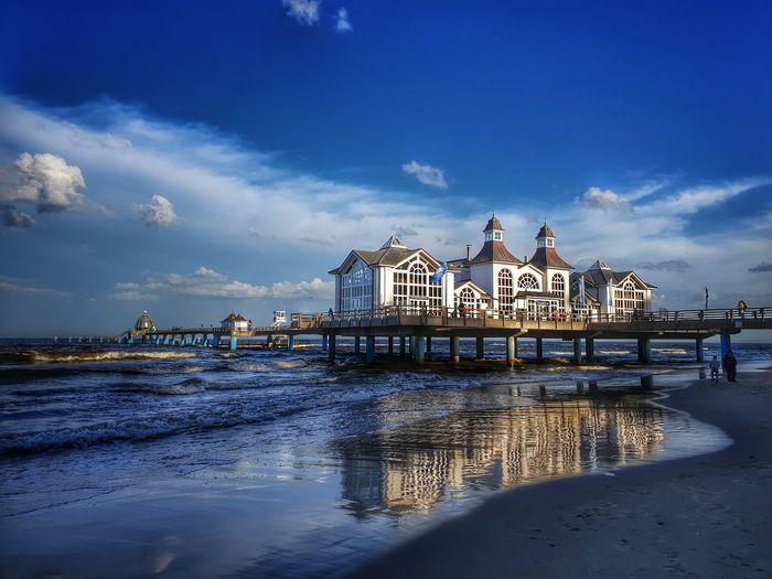 View of pier on beach against buildings