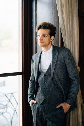 Portrait of young man standing against window