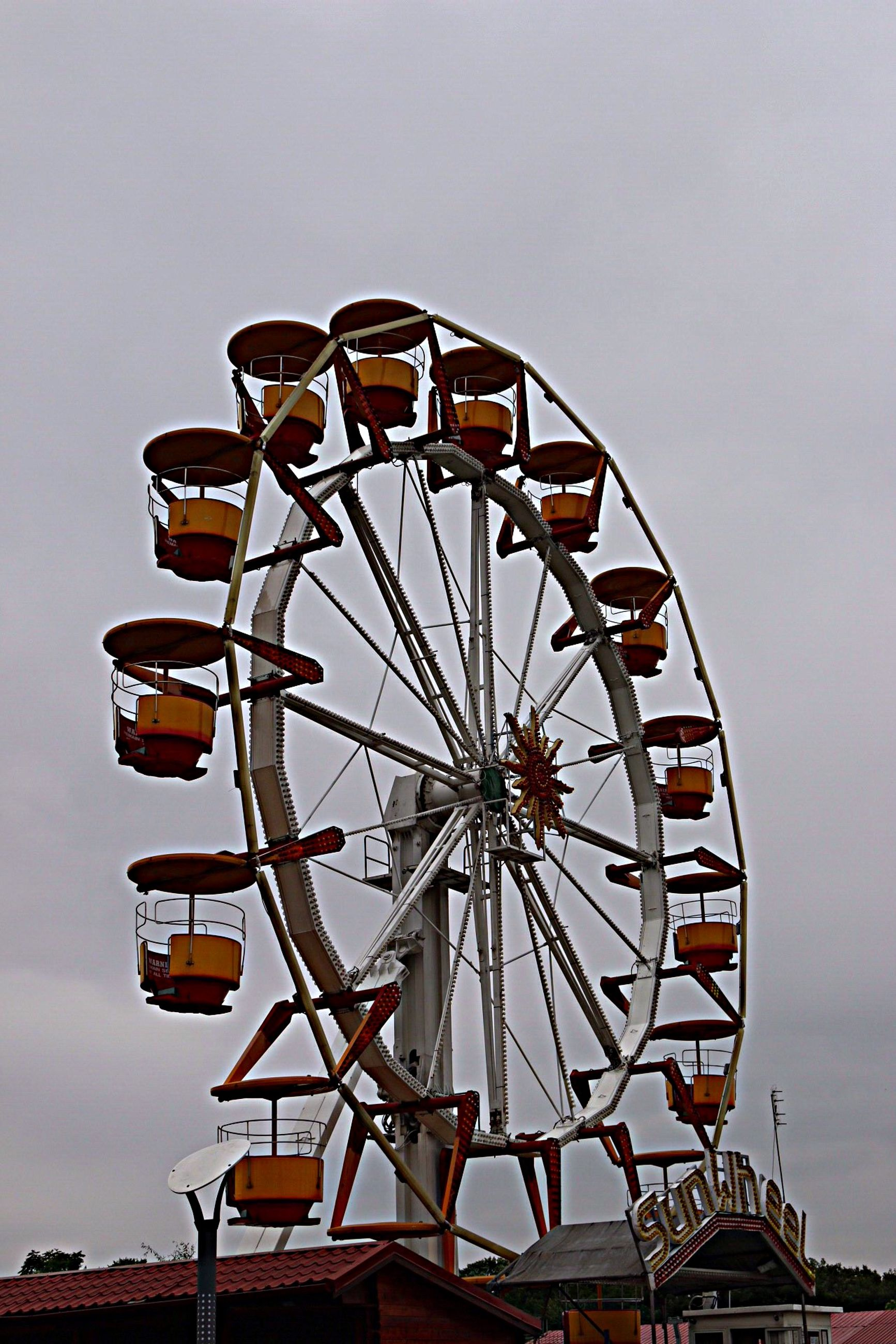 ferris wheel, amusement park, amusement park ride, arts culture and entertainment, low angle view, sky, built structure, architecture, circle, clear sky, wheel, day, outdoors, silhouette, large, cloud - sky, no people, metal, copy space, rollercoaster