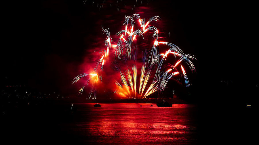 Arts Culture And Entertainment Blurred Motion Celebration Dark Entertainment Event Event Exploding Firework Firework - Man Made Object Firework Display Glowing Illuminated Light Long Exposure Motion Multi Colored Night No People Red Sparks Water Waterfront