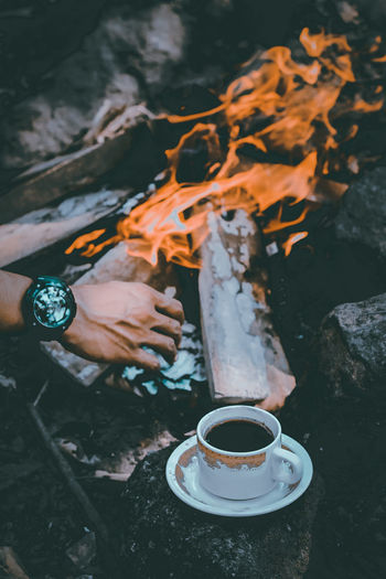Cropped hand of man over coffee by bonfire