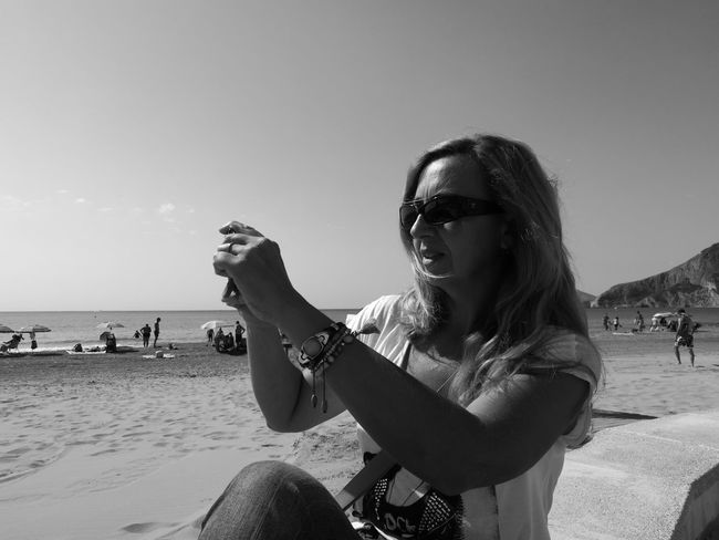 Women Who Inspire You People And Places Sea Beach Horizon Over Water Leisure Activity Lifestyles Water Enjoyment Sitting Clear Sky Holding Casual Clothing Outdoors Black And White Photography Black And White Portrait Black & White Portrait Of A Woman Portrait Photography Monochrome Photography