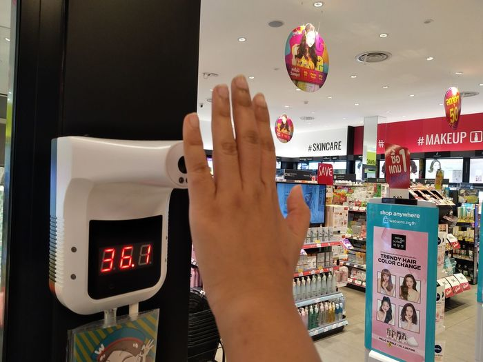 Close-up of woman hand using smart phone at store