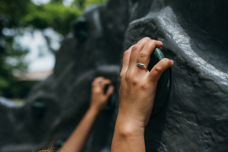 Cropped hand of woman climbing wall