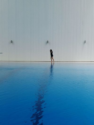 Woman Walking By Swimming Pool Against Wall