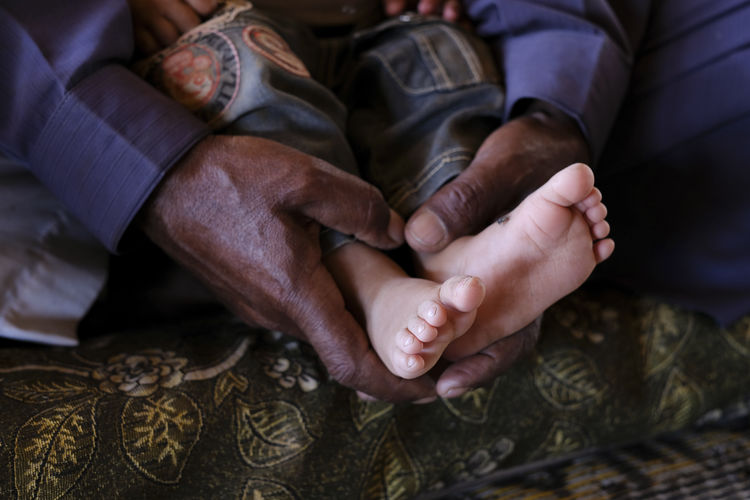 Cropped hands of grandfather holding grandchild legs
