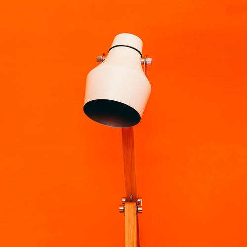 Low angle view of electric lamp against orange wall
