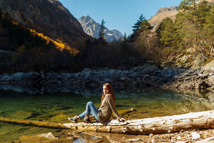 Woman sitting on rock by mountain