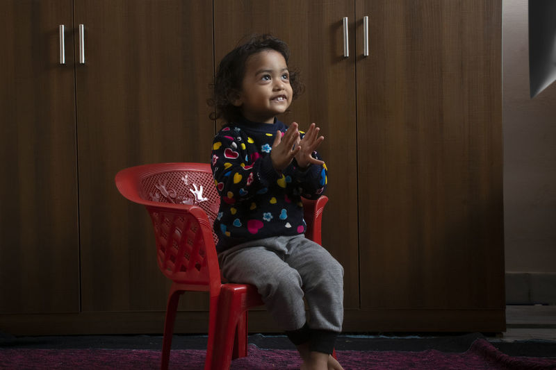 Smiling girl clapping hands while sitting on chair against closet