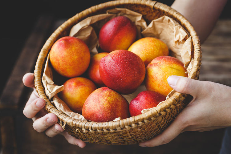 Cropped hands of woman holding wet peaches in basket