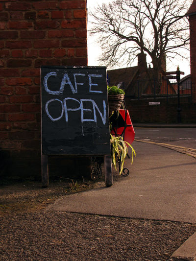 Open cafe sign by street in city