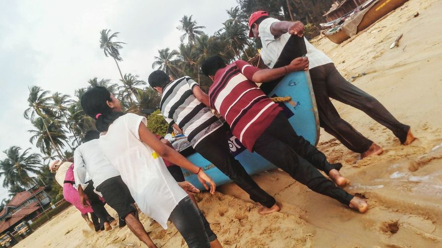 Striped Flag Outdoors Men People Full Length Adults Only Day Adult Togetherness Only Men Young Adult Togetherness👫👭 Pushing A Boat Helping Beach Fishing Boat Karwar Beach Karnataka