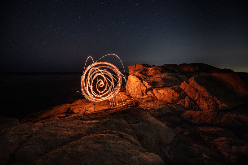 Light painting on rock formation against sky at night