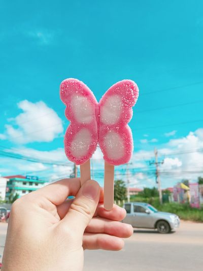 Close-up of hand holding pink butterfly shape candy against sky