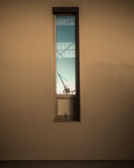 Crane Against Sky Seen Through Window