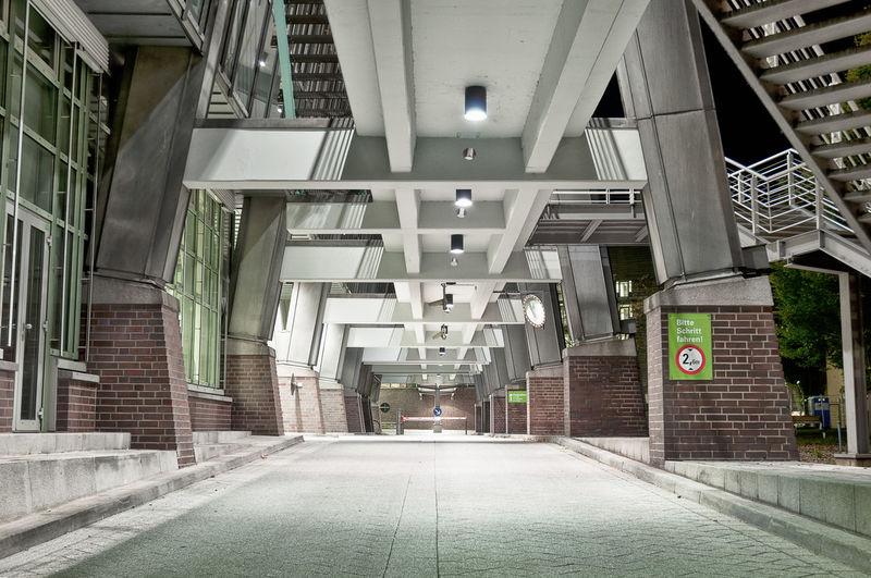 Empty Walkway Below Bridge By Building In City