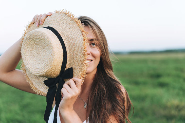 Portrait of smiling young woman holding hat on field against sky