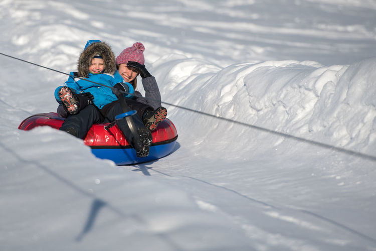 Portrait Of Mother And Son Tobogganing On Snow Covered Field