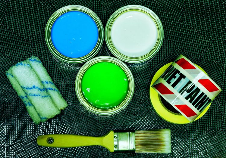 High angle view of paintbrush and cans on metal floor