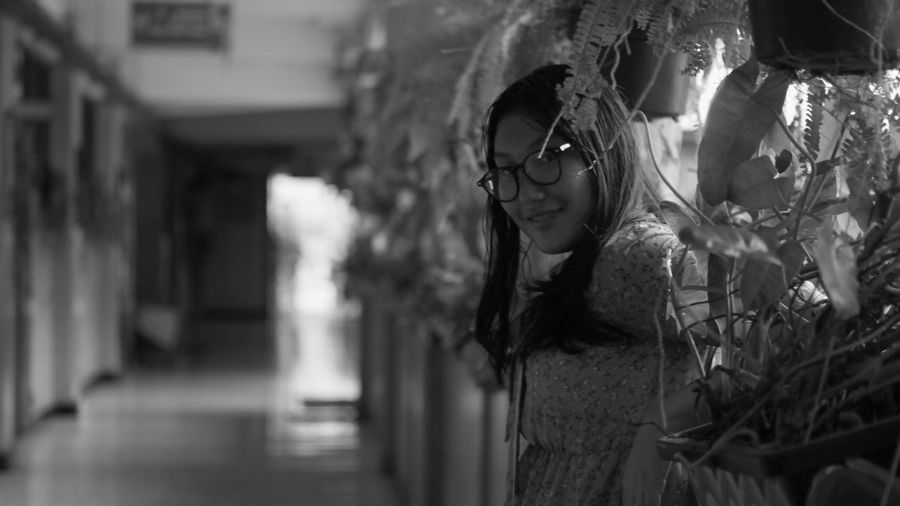 Portrait of young woman wearing sunglasses standing by plants in corridor