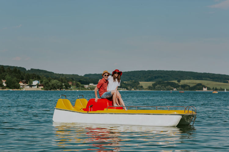 Portrait of smiling couple in love having fun pedal boating. Full length of young happy man and woman sitting on pedal boat. Boating Couple Date Holiday Horizontal Love Man Romantic Summertime Vacations Woman Young Boat Boyfriend Caucasian Day Girlfriend Lake Outdoors Pedalo Relax Sea Summer Two People Water
