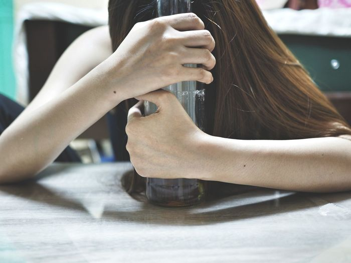 Close-up of depressed woman having alcohol at home
