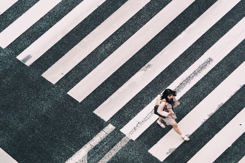AERIAL VIEW OF WOMAN CROSSING ZEBRA