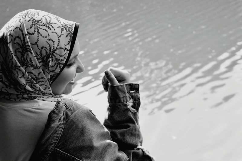 Side view of smiling woman wearing hijab by lake