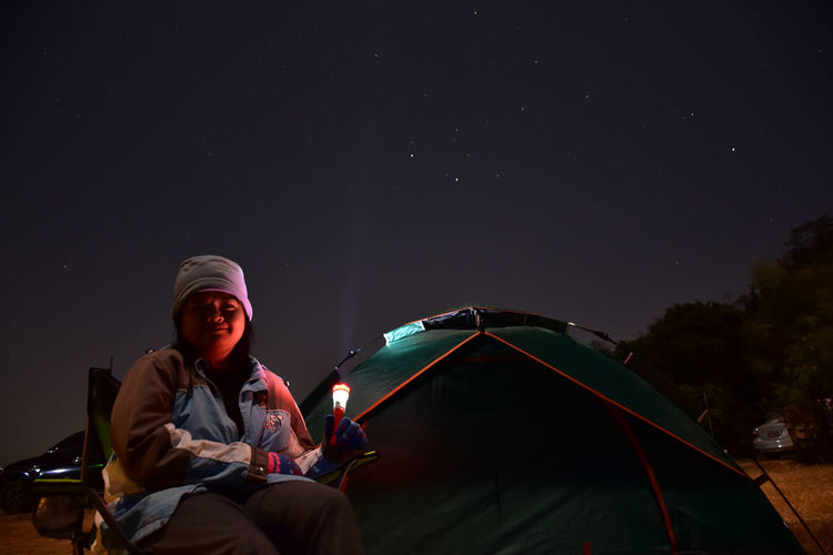 Man sitting by tent against sky at night
