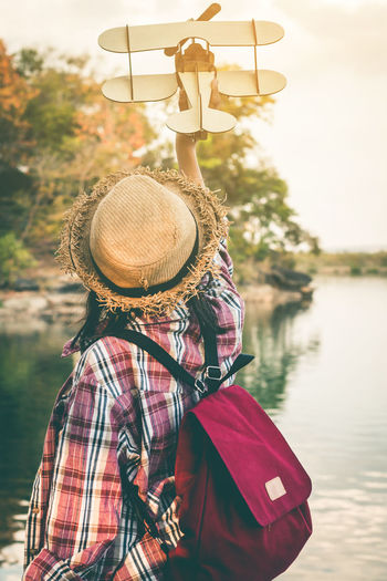 Rear view of girl holding model airplane while standing by lake