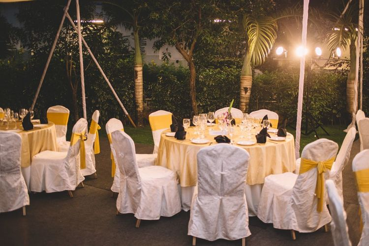 Dining tables arranged at backyard during dusk