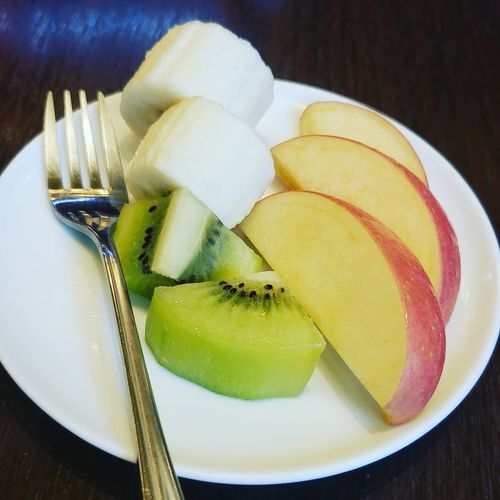 High angle view of chopped fruits in plate on table