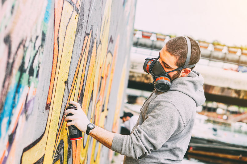 Side view of man photographing graffiti on wall