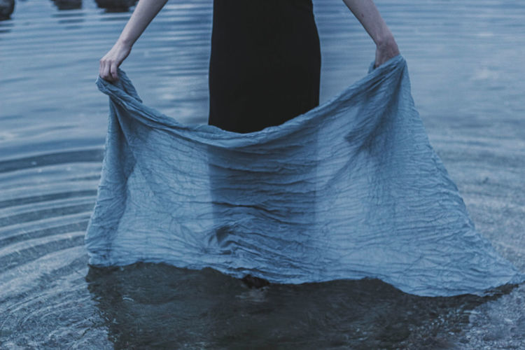 Low Section Of Woman Holding Textile While Standing In Sea