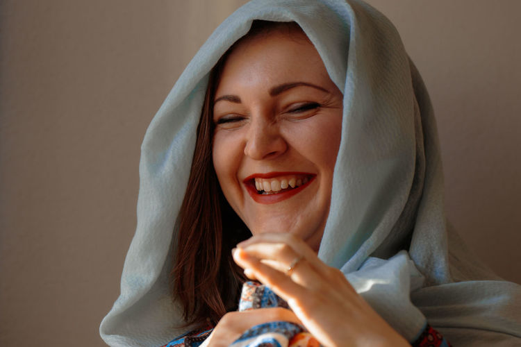 Close-up portrait of a smiling young woman holding ice cream