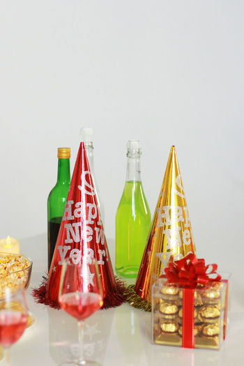Close-up of glass bottles on table against wall